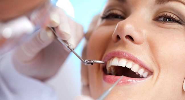 Woman with white smile having dental cleaning